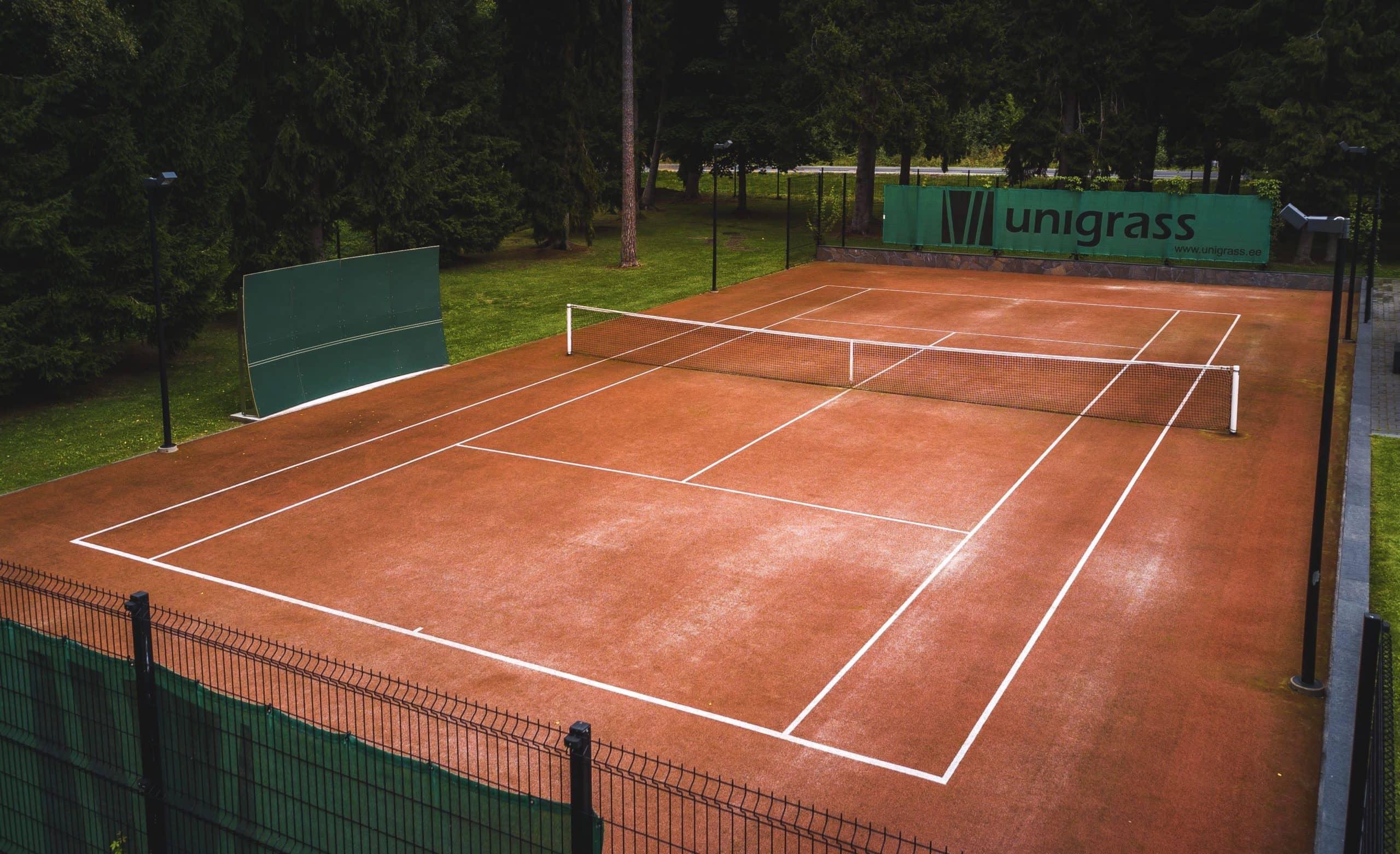 kunstmurukattega tenniseväljaku hooldus - hooldatud väljak rohelise tuuletõkkefooniga