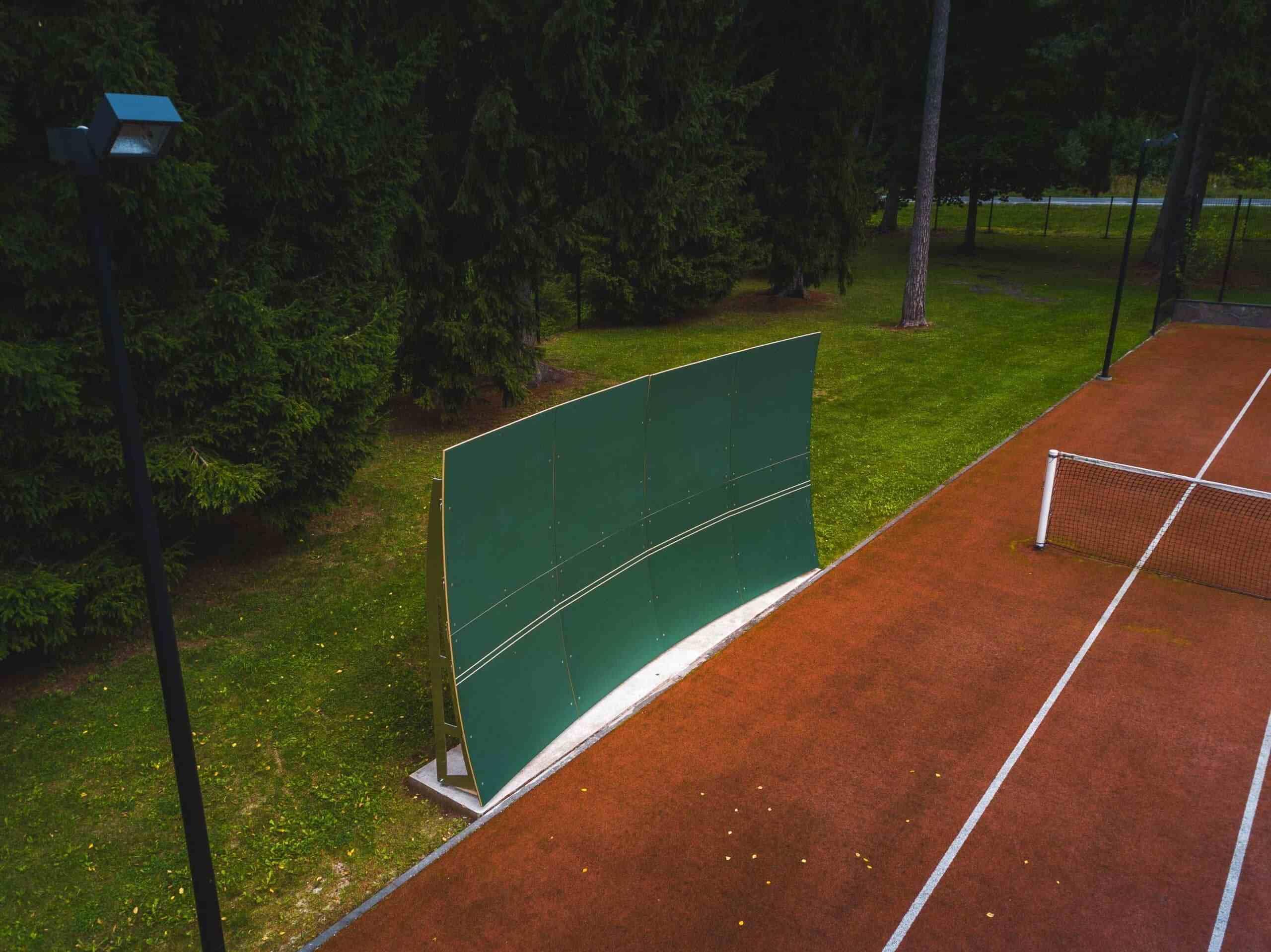Paraboone põrkesein kunstmuru kattega tenniseväljaku ääres