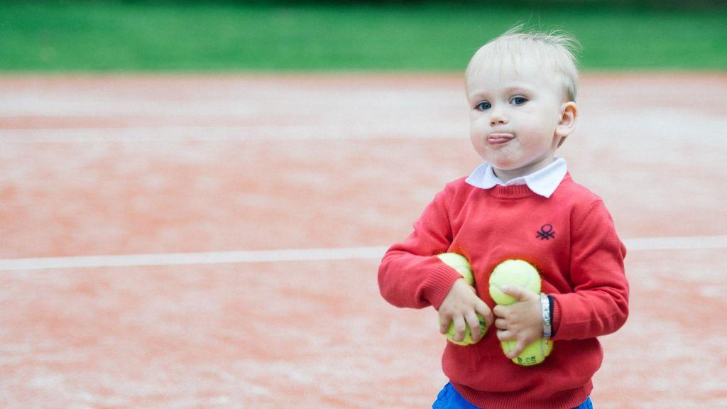 Tennis lastele: Punase kampsuniga poiss kunstmuru kattega tenniseväljakul