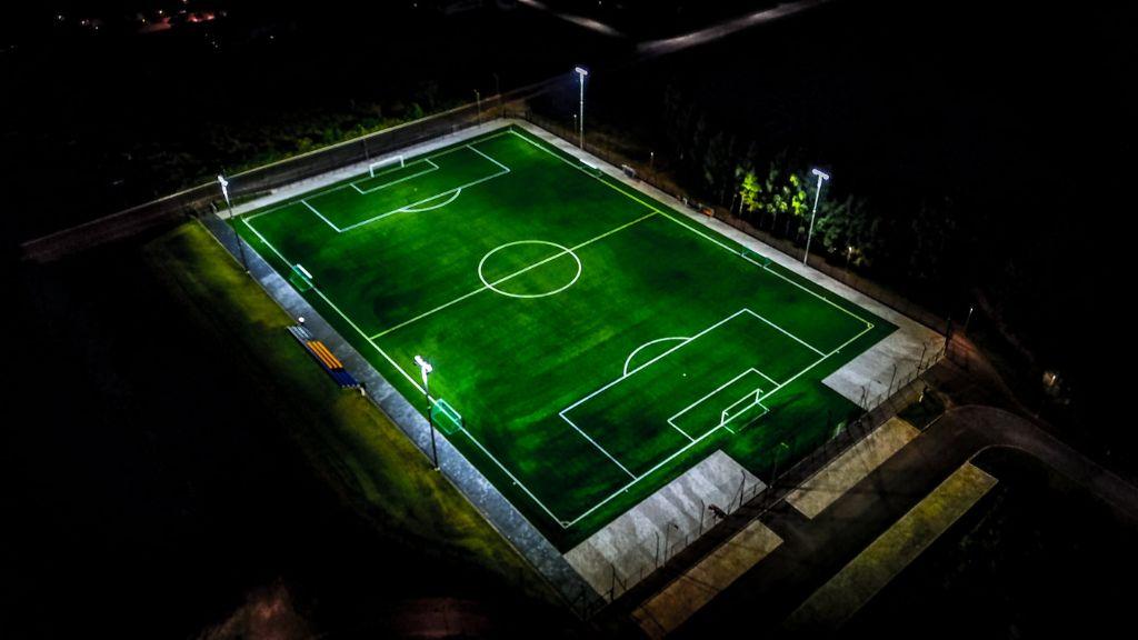 Jalgpalliväljaku kunstmuru öösel valgustatuna