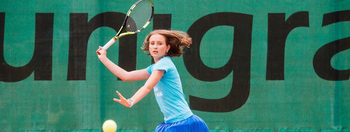Tüdruk mängib tennis Unigrassi tuuletõkke fooni ees