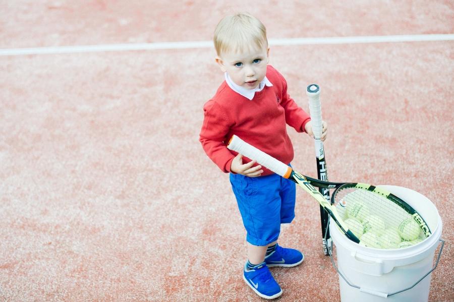 Poiss tennisereketite ja pallidega
